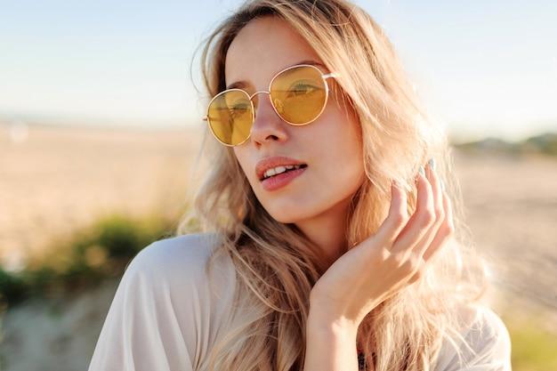 Schließen sie herauf porträt des verspielten lächelnden blonden mädchens, das mit haaren spielt, spaß hat und sommer am strand genießt.