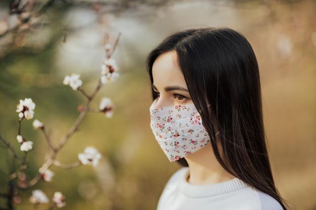 Schließen sie herauf porträt des zarten mädchens in einer weißen bluse unter einem blühenden aprikosenbaum mit einer maske mit blume