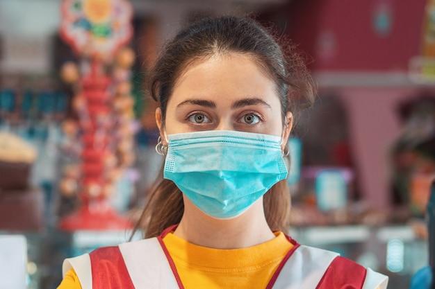 Schließen sie herauf porträt einer arbeiterin in uniform mit einer medizinischen maske. konzept vorbeugender maßnahmen während der coronavirus-pandemie.