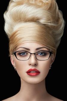Schließen sie herauf porträt einer blonden jungen frau in den gläsern, die die kamera betrachten