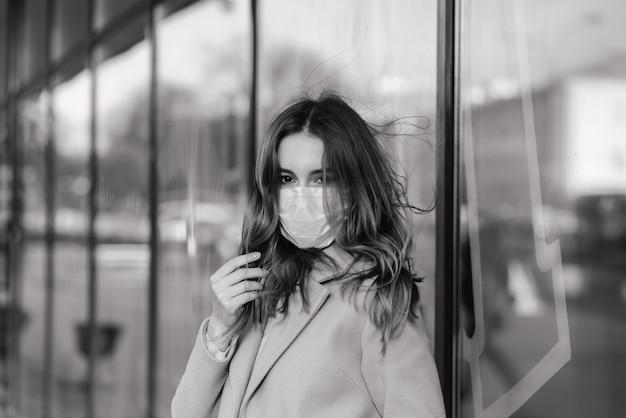 Schließen sie herauf porträt einer frau, die eine medizinische maske trägt und auf der straße gegen ein café steht