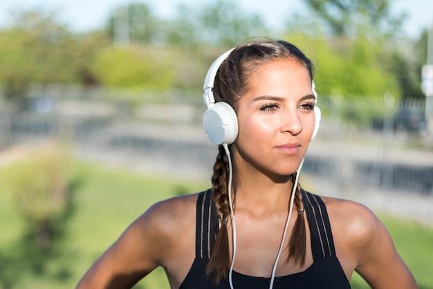 Schließen sie herauf porträt einer frau, die sport tut, der im freien lächelnd lächelt und musik hört