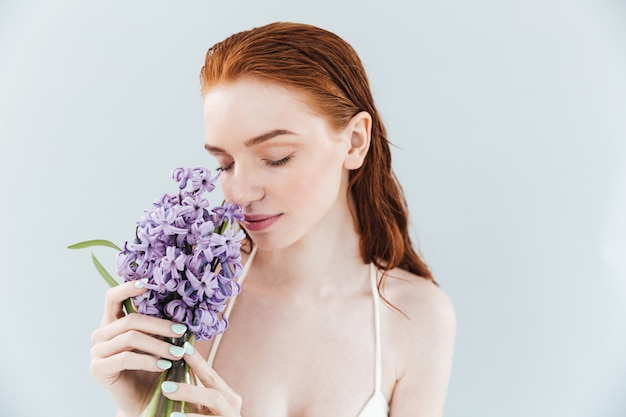 Schließen sie herauf porträt einer ingwerfrau, die hyazinthenblumen riecht