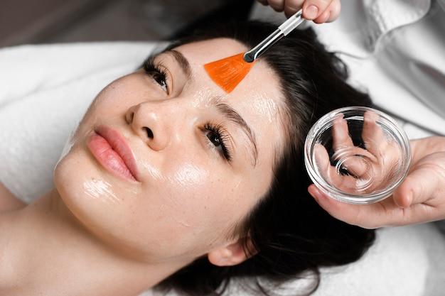 Schließen sie herauf porträt einer jungen reizenden frau mit dunklem haar, das sich auf ein spa-bett mit offenen augen stützt, während sie eine peeling-maske in einem spa-wellness-salon haben.
