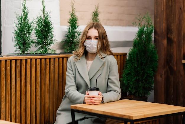 Schließen sie herauf porträt einer kaukasischen frau, die eine medizinische maske trägt und auf der straße gegen ein café steht