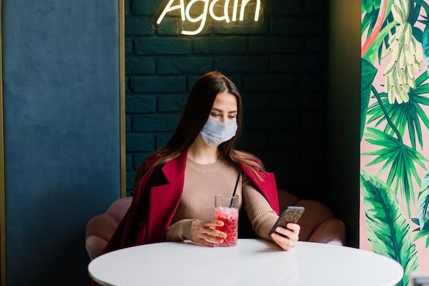 Schließen sie herauf porträt einer kaukasischen frau, die eine medizinische maske trägt und in der straße gegen hintergrund eines cafés steht