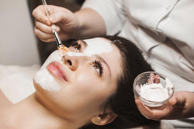 Schließen sie herauf porträt einer reizenden jungen frau, die eine weiße maske auf ihrem gesicht in einem wellness-spa-salon tut.