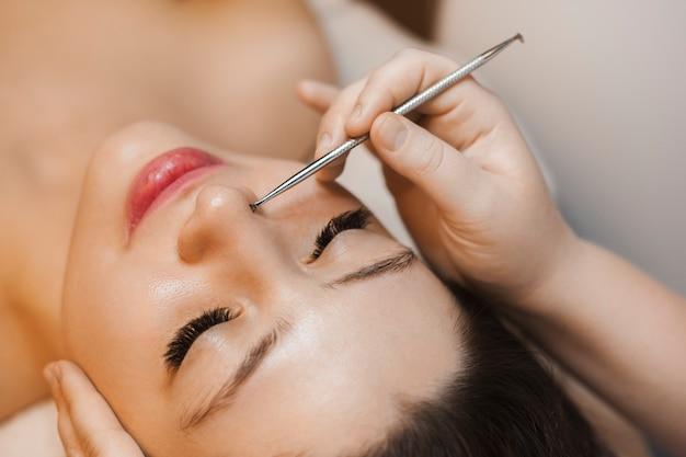Schließen sie herauf porträt einer reizenden jungen kaukasischen frau, die gesichtsreinigung durch kosmetikerin in einem wellness-salon hat.