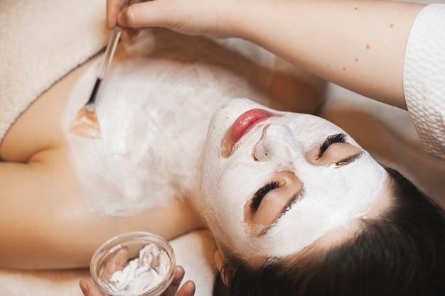 Schließen sie herauf porträt einer schönen jungen kaukasischen frau, die eine weiße organische hautpflegemaske auf ihrem gesicht hat, während ihre kosmetikerin aloe auf den hals anwendet.