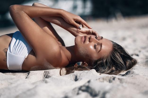 Schließen sie herauf porträt einer sexy jungen frau, die auf einem weißen sandstrand niederlegt, der einen luxuriösen bikini trägt