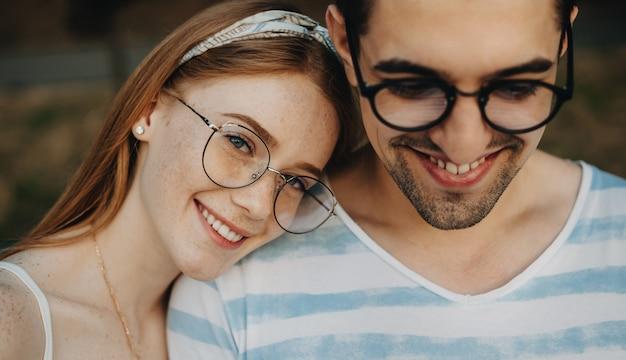 Schließen sie herauf porträt eines charmanten paares, in dem mädchen ihren kopf auf die schulter seines freundes lehnt und kamera lächelnd betrachtet, während er lächelnd nach unten schaut.