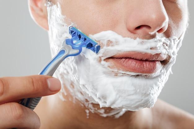 Schließen sie herauf porträt eines ernsten mannes mit dem rasieren des schaums