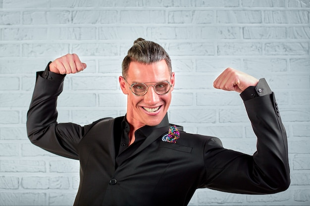 Schließen sie herauf porträt eines glücklichen jungen geschäftsmannes, der brille trägt, die in einem schwarzen anzug gekleidet zeigt hände kühl