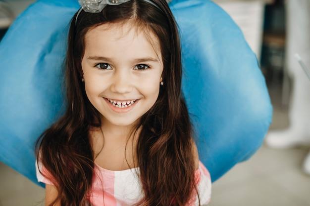 Schließen sie herauf porträt eines glücklichen kleinen mädchens lächelnd, das in einem stomatologischen stuhl sitzt. schönes kind nach einer zahnoperation.