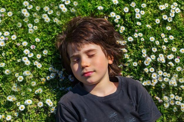Schließen sie herauf porträt eines jungen, der auf einer lichtung mit gänseblümchen liegt und augen mit vergnügen schließt.