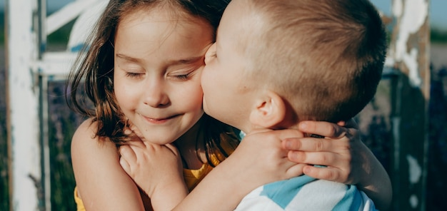 Schließen sie herauf porträt eines kaukasischen blonden jungen und seiner schwester, die sie küssen und gegen den sonnenuntergang umarmen