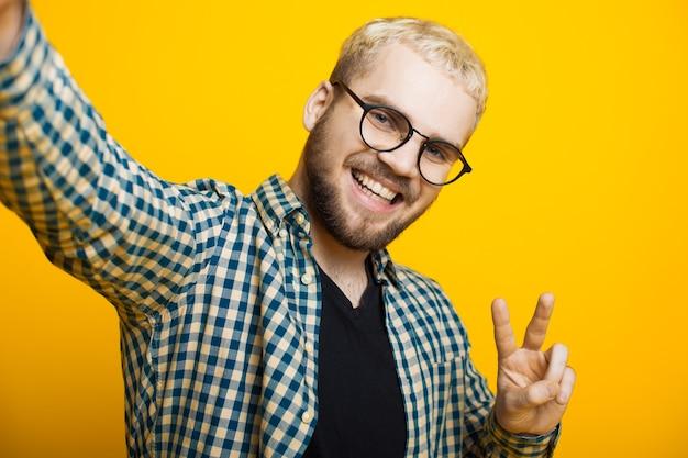 Schließen sie herauf porträt eines kaukasischen mannes mit blondem haar und kurzem bart, der durch brillen schaut und ein selfie macht