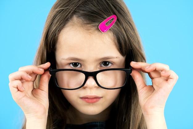 Schließen sie herauf porträt eines kinderschulmädchens, das schauende brille lokalisiert auf blau trägt