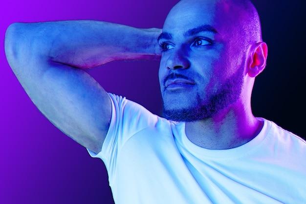 Schließen sie herauf porträt eines mannes im lila neonlicht im studio