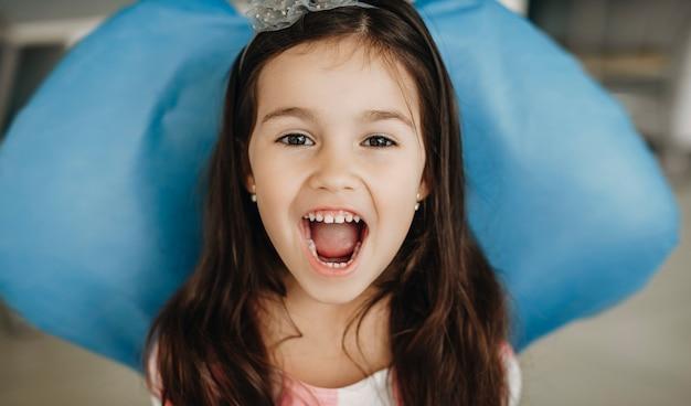 Schließen sie herauf porträt eines niedlichen kleinen mädchens, das in einem stomatologiesitz sitzt, der kamera betrachtet, zeigen zähne nach zahnoperation in einer pädiatrischen stomatologie.