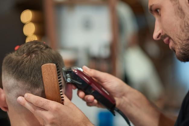 Schließen sie herauf porträt eines professionellen friseurs, der mit seinem klienten arbeitet, der ihm einen haarschnitt gibt.
