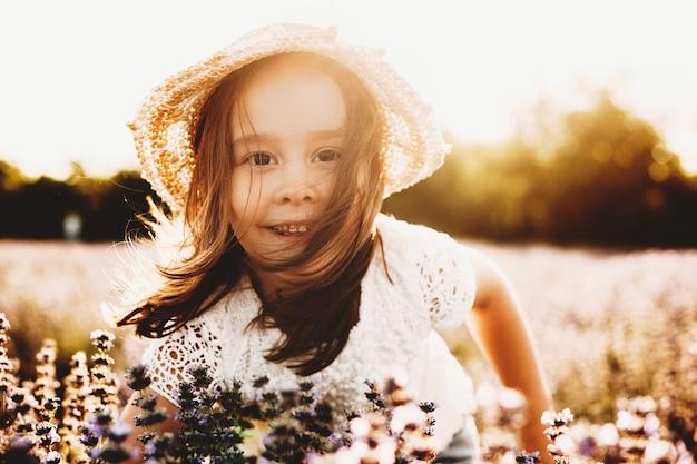 Schließen sie herauf porträt eines reizenden kleinen mädchens, das draußen gegen sonnenuntergang lächelt. nettes kleines kind, das kamera glücklich gegen sonnenuntergang im feld der blumen betrachtet.