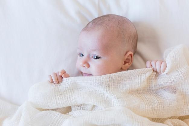 Schließen sie herauf porträt eines schönen babys auf dem weißen hintergrund, der zu hause mit einer decke bedeckt wird
