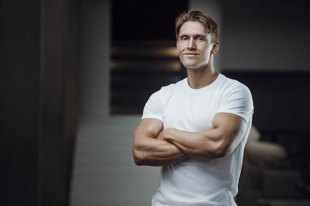 Schließen sie herauf porträt eines schönen fitnessmannes im weißen hemd im fitnessstudio. muskeltraining fitness und bodybuilding-konzept