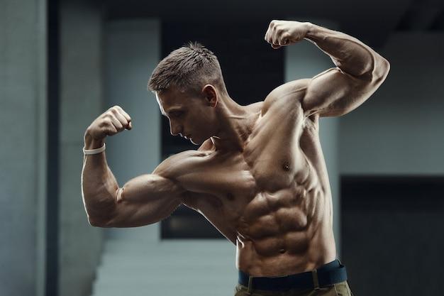 Schließen sie herauf porträt eines schönen fitnessmannes im weißen hemd im fitnessstudio.