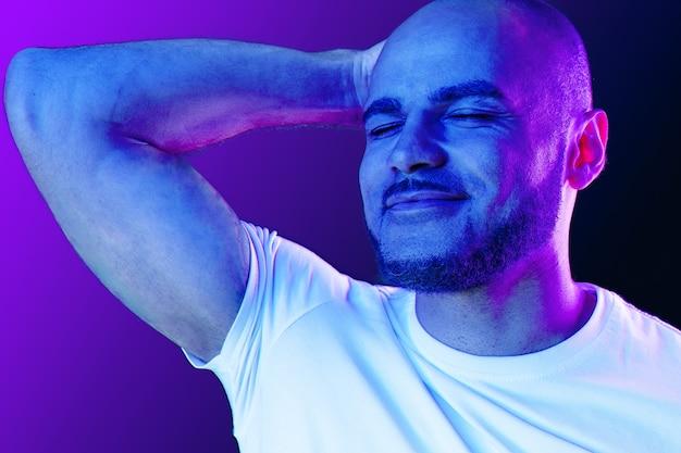 Schließen sie herauf porträt eines schwarzen mannes im lila neonlicht im studio