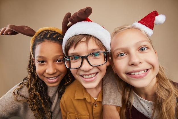 Schließen sie herauf porträt von drei kindern, die weihnachtsporträts tragen und in die kamera lächeln, während sie gegen sein hintergrund im studio stehen