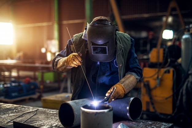 Schließen sie herauf porträtansicht des professionellen fokussierten maskengeschützten schweißers in der uniform, die an der metallskulptur am tisch in der sonnigen industriellen stoffwerkstatt arbeitet.