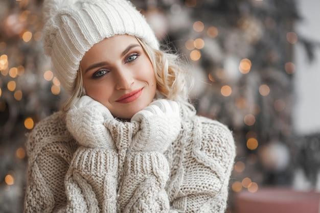 Schließen sie herauf portrait der schönen frau auf weihnachtsszene. junges mädchen nahe den weihnachtsbaumlichtern