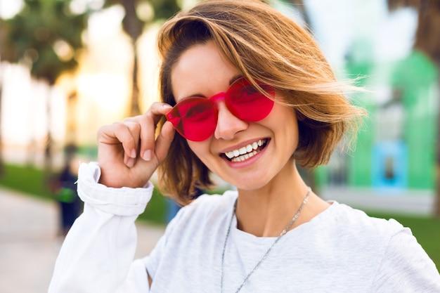 Schließen sie herauf positives porträt der fröhlichen jungen frau lächelnd und lachend, positive mode