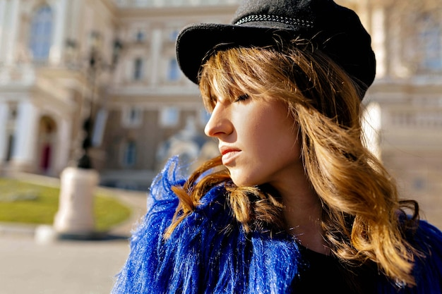 Schließen sie herauf profilporträt außerhalb der zarten frau in der schwarzen kappe und im blauen mantel, die sonne mit lächeln genießen