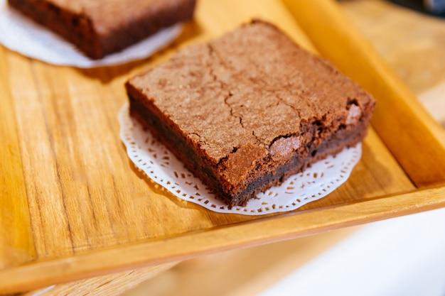 Schließen sie herauf quadratische brownie chocolate cakes auf hölzernem behälter, der bereit ist zu verkaufen. schmelze in deinem mund.