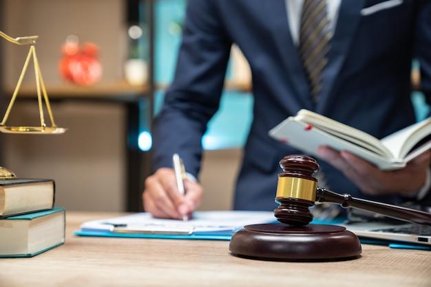 Schließen sie herauf rechtsanwalt geschäftsmann, der gesetzbuch im büroarbeitsplatz für beraterrechtskonzept arbeitet oder liest