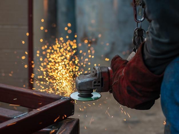 Schließen sie herauf reibendes metall der schrotarbeitskraft und schweißensmetall mit vielen feuerfunken