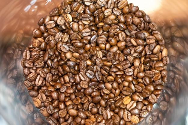Schließen sie herauf röstkaffeebohnen der draufsicht im trichter für hintergrund