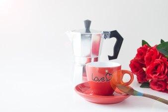 Schließen Sie herauf rote Kaffeetasse auf weißem Hintergrund mit Rotrose und Kaffeetopf