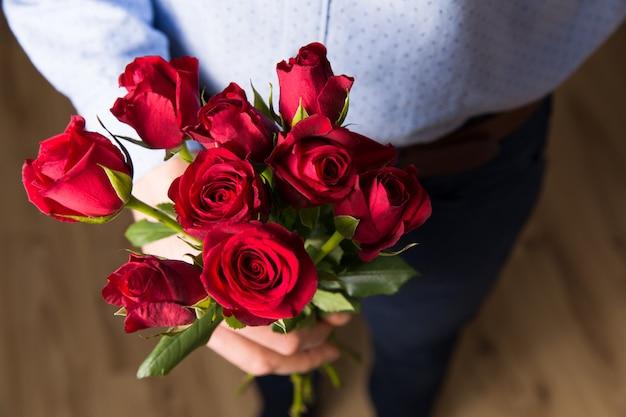 Schließen sie herauf rote rose, romantische überraschungsblumen des gutaussehenden mannes valentinstag.