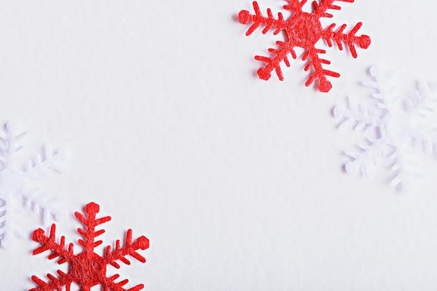 Schließen sie herauf rote und weiße schneeflocke auf weißem hintergrund, weihnachtswinterdekorelement