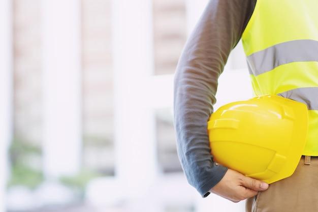 Schließen sie herauf rückansicht des technischen männlichen bauarbeiterstandes, der gelben sicherheitshelm hält und reflektierende kleidung für die sicherheit des arbeitsvorgangs trägt. außerhalb des gebäudetisches.