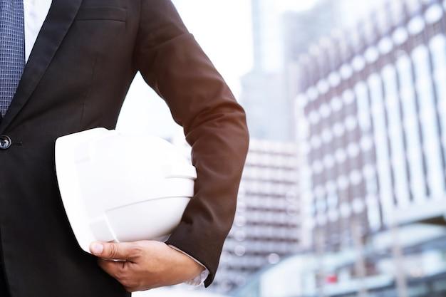 Schließen sie herauf rückansicht des technischen männlichen bauarbeiterstandes, der weißen sicherheitshelm hält und reflektierende kleidung für die sicherheit des arbeitsvorgangs trägt. im freien des gebäudehintergrunds.