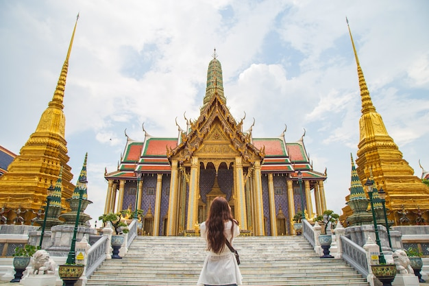 Schließen sie herauf rückseitiges porträt junge asiatische frau, die vor der goldenen kirche innerhalb wat phra kaew steht, es gibt einen der beliebtesten tempel in bangkok thailand.