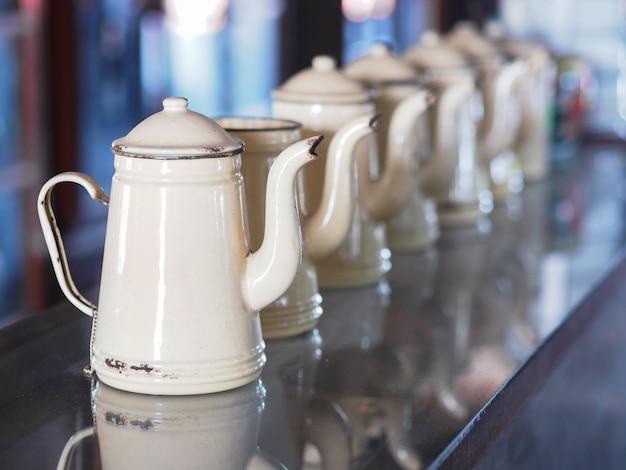 Schließen sie herauf rustikale teekanne der cremefarbenen weinlese, die auf glastisch gesetzt wird.