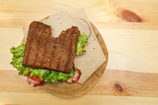 Schließen sie herauf saftiges gebissenes sandwich mit speck