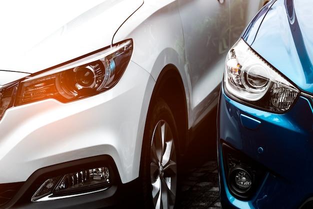 Schließen sie herauf scheinwerferlicht des blauen und weißen suv-autos, das auf konkretem parkplatz des hotels oder des einkaufszentrums geparkt wird. automobilindustrie-konzept. elektro- oder hybridautotechnik. mietwagen-konzept.