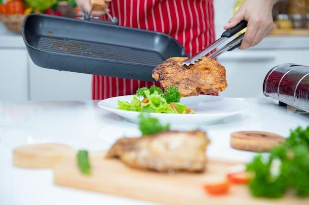 Schließen sie herauf, schöne asiatische frau, die gegrilltes schweinesteak von der pfanne mit grünem eichengemüse in der schale hält. ideen für gesundes kochen und gewichtsverlust.
