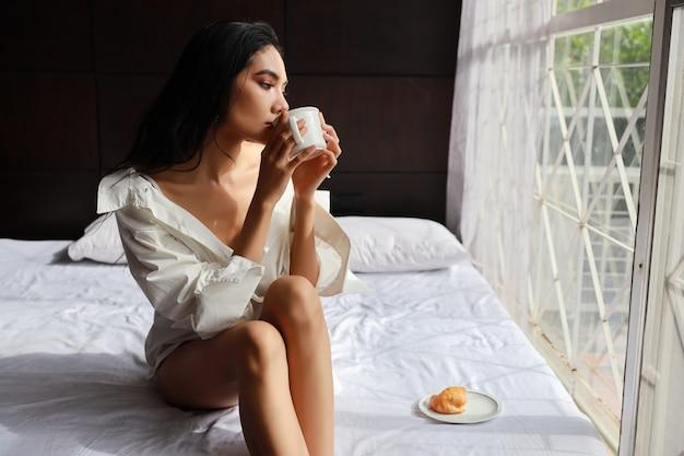 Schließen sie herauf schöne asiatische frau im sexy kleid, das kaffee und hörnchen beim sitzen im bett frühstückt